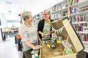 Die Pro-Manu-Vorstandsmitglieder Barbara Rossbacher und Yvonne Joos in der Bibliothek der PHTG. Die dort ausgestellten Koffer haben Lehrerinnen für textiles und technisches Gestalten für die Jubiläumsversammlung des Vereins gemacht. (Bild: Donato Caspari)