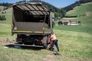 Zwei Polizisten untersuchen den verunfallten Lastwagen der Armee (Bild: Peter Schneider / Keystone)