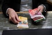 An einem Bankschalter wird Geld gezählt. (Corinne Glanzmann, Luzern, 18. Januar 2018)