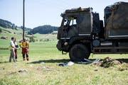 Personen untersuchen einen verunfallten Lastwagen der Armee in Linden bei Oberdiessbach. (Bild: Keystone/ Peter Schneider, 16. Juli 2018)