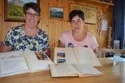 Die amtierende Aktuarin Annelies Jud (links) und die Präsidentin Ursi Jäger mit den historischen, handschriftlich geführten Protokollbüchern des Vereins. (Bild: Adi Lippuner)