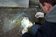 Ein Beamter der Spurensicherung der Kantonspolizei St. Gallen untersucht eine eingeschlagene Fensterscheibe. (Symbolbild: Urs Bucher)