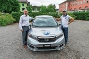 Reto Flury vom OK (mit Kappe) und Vital Hotz von der Auto Hotz AG präsentieren den Hauptpreis der Dorf-Fäscht-Tombola. (Bild: PD)