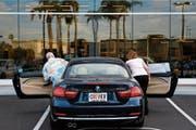Ein amerikanische Paar steigt zur Probefahrt in ein Modell des deutschen Herstellers BMW. (Bild: Patrick T. Fallon/Bloomberg (Santa Ana, 2. Juni 2014))
