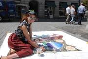 Die junge Künstlerin Lena Eberhard malt während einer Woche ihre Traumwelt auf die Strassen St.Gallens. (Bild: Corinne Bischof)