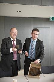 Stadtrat Fredy Brunner und Projektleiter Marco Huwiler zeigen Trümmerstücke aus dem Bohrloch. (Bild: Urs Jaudas, 27. September 2013)