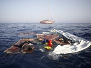 Überreste eines Flüchtlingsboots im Mittelmeer vor der Küste Libyens: Im Wasser treiben auch zwei Leichen. (Bild: KEYSTONE/AP)