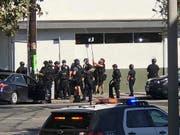 Polizisten versuchen mit einem Spiegel einen Blick ins Innere des Supermarkts zu erhalten. (Bild: KEYSTONE/AP Christian Dunlop)