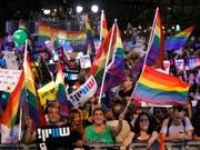 In Israel sind am Sonntag Tausende mit Regenbogenfahnen auf die Strasse gegangen, um gegen ein neues Gesetz zu protestieren. (Bild: KEYSTONE/EPA/ABIR SULTAN)