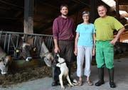 Reto, Gaby und Werner Eigenmann stehen mit ihrem Hofhund, dem Border Collie Odine, in der Scheune bei den Kühen. (Bild: Yvonne Aldrovandi-Schläpfer)
