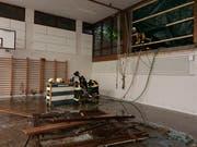 Feuerwehrleute pumpen Wasser aus der überfluteten Turnhalle der Schulanlage Reutenen.