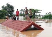 Bewohner retten sich auf ihre Hausdächer, nachdem das ausgetretene Wasser mehrere Dörfer geflutet hat. (Bild: ABC Laos News / EPA, 24. Juli 2018)