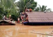 Dorfbewohner in Laos warten auf einem Hausdach auf ihre Rettung. (Bild: EPA/ABC LAOS NEWS, 24. Juli 2018)