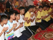 Die aus einer Höhle in Thailand geretteten Jugendlichen vollziehen ein buddhistisches Reinigungsritual nach ihren negativen Erfahrungen. (Bild: KEYSTONE/AP/SAKCHAI LALIT)
