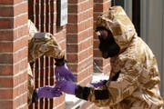 Specialist team members in military protective suits use a jar in the front doorway as they search the fenced off John Baker House for homeless people on Rollestone Street in Salisbury, England, Friday, July 6, 2018. British police are scouring sections of Salisbury and Amesbury in southwest England, searching for a container feared to be contaminated with traces of the deadly nerve agent Novichok. (AP Photo/Matt Dunham)