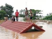 Nach dem Bruch eines Staudamms haben sich Dorfbewohner in Laos auf das Dach eines überfluteten Hauses gerettet. (Bild: KEYSTONE/EPA ABC LAOS NEWS)