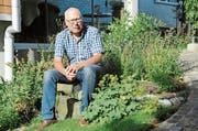 Hanspeter Horsch in seinem heimischen Garten. Neben ihm die Pflanze Frauenmantel, die vor allem bei Zyklusbeschwerden Abhilfe schafft. (Bild: Astrid Zysset)