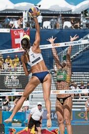 Die US-Amerikanerin Emily Stockman im Angriff gegen die Brasilianerin Agatha im Viertelfinal des Gstaader Beachvolleyball-Turniers. (Bild: Peter Schneider/Keystone (14. Juli 2018))