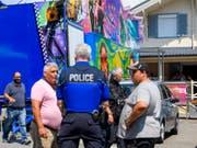 Versuch einer Einigung: Polizisten diskutieren mit Schaustellern vor dem Haus, das in Versoix verbotenerweise gebaut worden ist. (Bild: Keystone/MARTIAL TREZZINI)