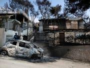 Das Drama im Osten Athens um die Hafenstadt Rafina geht weiter. Freiwillige Helfer und die Feuerwehr entdecken immer wieder neue Opfer in den verbrannten Häusern des ehemaligen Ferienparadieses. (Bild: Keystone/AP/THANASSIS STAVRAKIS)