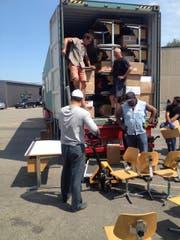 Die Helfer beladen einen Schiffscontainer mit Schulmobiliar. (Bild: Anita Fahrni)