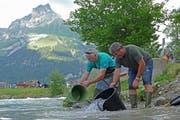 Wildhüter Klaus Hurschler (rechts) und Winfried König von der Forellenfarm Luterbach in Ennetmoos setzen Bach- und Regenbogenforellen aus. (Bild: Beat Christen (Engelberg, 16. Juli 2018))