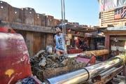 Der Bauarbeiter in der Grube befestigt den mit Lehm gefüllten Wagen am Kranenhaken, welcher das Material anschliessend in eine Mulde leert.