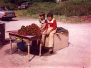 Beat Walker (links) mit seinem Cousin Markus beim Alpenrosenverkauf in der Schöni; hinten im Gebüsch das alte Auto, das ihnen bei Regen Schutz bot. (Bild: PD)