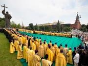 Die Taufe der Rus: Orthodoxe Priester an einer Zeremonie vor einer Statue von Fürst Wladimir in Moskau. (Bild: KEYSTONE/EPA AP POOL/ALEXANDER ZEMLIANICHENKO / POOL)