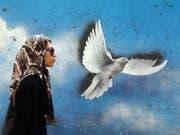 Irans Frauen wollen keinen Kopftuchzwang mehr: Frau vor einem Wandgemälde in Teheran. (Bild: KEYSTONE/EPA/ABEDIN TAHERKENAREH)
