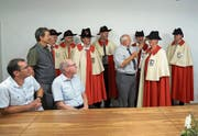 Giswils alt Gemeindeweibel Hanspeter Schnider übergibt seiner Nachfolgerin Esther Windlin-Berchtold die Amtstracht. Die Weibel aller Obwaldner Gemeinden sind mit dabei. (Bild: Romano Cuonz (Giswil, 2. Juli 2018))