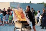 Unter Anleitung löscht eine Besucherin eine brennende Pfanne. (Bild: Barbara Hettich)