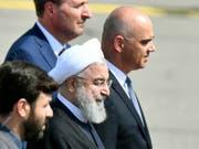 Der iranische Präsident Hassan Ruhani (Mitte, mit Kopfbedeckung) nach seiner Begrüssung durch Bundespräsident Alain Berset (rechts) auf dem Flughafen Zürich-Kloten. (Bild: KEYSTONE/WALTER BIERI)