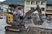 Nach dem offiziellen Teil durften auch die Schüler ran: Unter Anleitung von Remo Krummenacher bedient Laurin den Bagger. (Bild: Birgit Scheidegger (Sachseln, 3. Juli 2018))