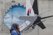 Eine Frau läuft am Wandbild zur Erinnerung an den Absturz des MH370-Fluges vorbei. (Bild: EPA/ Fazry Ismail, Kuala Lumpur, 29. Juli 2018)