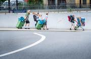 Ein paar Hip-Hop-Fans schleppen ihr Gepäck in Grüntonnen in Richtung Open-Air-Gelände. (Bild: Andrea Stalder)