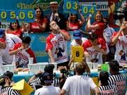 Der Serien-Champion Joey Chestnut (Mitte) verbesserte seinen Rekord vom Vorjahr um zwei Hotdogs. (Bild: KEYSTONE/EPA/PETER FOLEY)