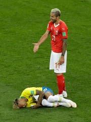 Neymar wälzt sich im Spiel gegen die Schweiz am Boden - Valon Behrami versteht es nicht. (Bild: Keystone)