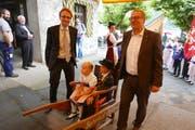 Der Urner Regierungsrat Urs Janett (links) und der Nidwaldner Regierungsrat Alfred Bossard eröffnen in Seelisberg den neuen Wanderweg, indem sie symbolisch zwei Trachtenkinder auf einer Sänfte trugen. (Bild: PD).