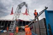 Mitarbeiter tragen Elemente der Zuschauertribüne unter das Zelt des Zirkus Knie (Bild: Corinne Glanzmann (Luzern, 5. Juli 2018))