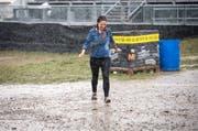 Eine Besucherin kämpft sich durch Regen und Schlamm.