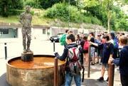 Auf einem Sockel im Brunnen steht eine lebensgrosse Figur aus rostigem Stahl.