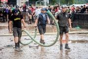 Helfer sind mit Saugschläuchen auf dem Festivalgelände unterwegs.