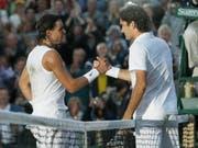 Ein Bild für die Ewigkeit: Auf dem schon sehr dunklen Centre Court von Wimbledon gratuliert Roger Federer (re.) Rafael Nadal zum Sieg (Bild: KEYSTONE/AP/ANJA NIEDRINGHAUS)