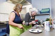 Therapeutin Silke Thomson (links) dekoriert mit Bewohnerin Verena Jolanda Schuler Muffins. (Bild: Werner Schelbert (Oberwil, 27. Juli 2018))