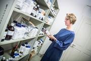 Apothekerin Claudia Held, Inhaberin der Rathausapotheke, ordnet im Untergeschoss Chemikalien ins Regal, die sie für ihre unterschiedlichsten Rezepturen benötigt. (Bilder: Andrea Stalder)