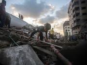 In Trümmer gelegt: Palästinenser in der von Israels Luftwaffe zerstörten mutmasslichen Hamas-Sicherheitszentrale in Gaza. (Bild: KEYSTONE/EPA/HAITHAM IMAD)