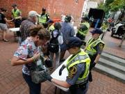 Die Polizei in Charlottesville kontrolliert Taschen. Zum Jahrestag der tödlichen Ausschreitungen an diesem Sonntag haben die Stadt Charlottesville und der Bundesstaat Virginia aus Sorge vor neuen Zwischenfällen den Notstand ausgerufen. (Bild: KEYSTONE/AP/STEVE HELBER)