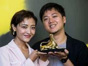Die chinesische Schauspielerin Luna Kwok und der singapurische Regisseur Siew Hua Yeo posieren in Locarno mit dem Goldenen Leoparden für den Siegerfilm «A Land Imagined». (Bild: Keystone/ALEXANDRA WEY)
