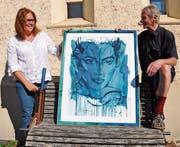Karin Noser und Armin Nüesch mit dem Kunstdruck, der auf der Bank abgelegt worden war. Bild: acp